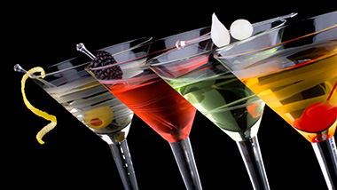 Four filled martini glasses lined up in a row, they all appear to be different types of drinks.