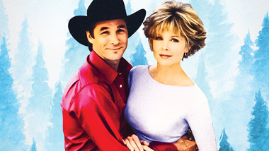 Clint Black wearing a red shirt and black cowboy hat fondly hugging Lisa Hartman Black in front of a snowy white forest background.