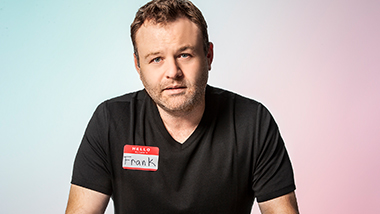 Frank is wearing a black v-neck and looking at you confused.  He is wearing a name tag to let you know that his name is Frank.  He is positioned in front of a multi-color background.