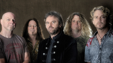 The band, 38 Special, is posing for a group photo in front of a grey background.  They look very serious about their music.