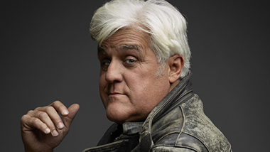 Close up of Jay Leno looking into the camera on a dark gray background.