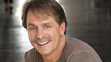 Jeff Foxworthy in a grey t-shirt smiling in a sauve manner at the camera as his mustache gleems in the light