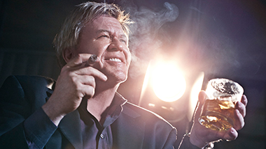 Ron White holding a cigar in one hand and a beverage in the other.