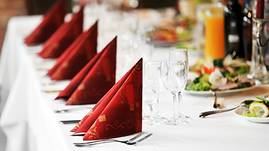 Banquet table with elegant table setting with linens napkins glasses and silverware